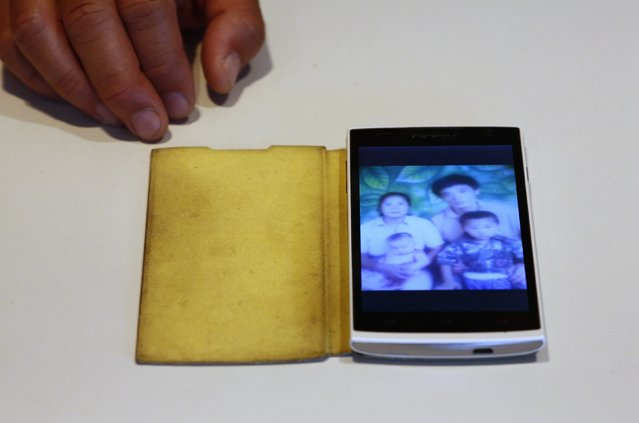 Liu Kun, whose younger brother Liu Qiang was onboard Malaysia Airlines Flight MH370 which disappeared on March 8, 2014 shows a picture of his brother (top, R) on his mobile phone during an interview with Reuters in Beijing July 18, 2014. Liu said he does not believe that the vanished plane crashed in the Indian Ocean losing all people on board. He wishes his brother and other people onboard the plane are still alive. (Photo by Kim Kyung-Hoon/Reuters)