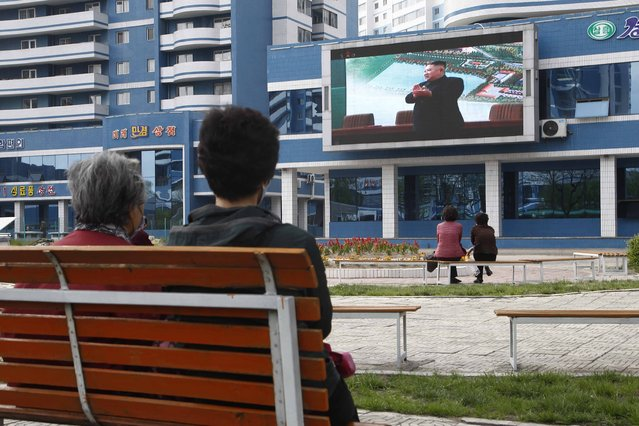 People in a park watch news broadcasted on a giant screen showing leader Kim Jong Un attending the opening ceremony of the Sunchon Phosphatic Fertilizer Factory  Saturday, May, 2nd. 2020, in Pyongyang, North Korea. Un made his first public appearance in 20 days as he celebrated the completion of a fertilizer factory near Pyongyang, state media said Saturday, ending an absence that had triggered global rumors that he may be seriously ill. (Photo by Jon Chol Jin/AP Photo)