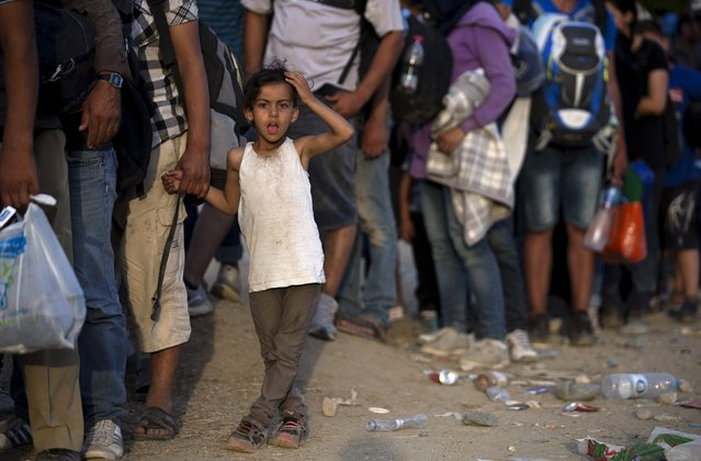 A migrant girl reacts as she waits with her parents to enter a camp for registration procedures after crossing the Macedonian-Greek border near Gevgelija, Macedonia, September 5, 2015. (Photo by Stoyan Nenov/Reuters)