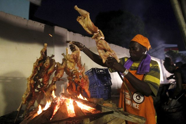 A cook grills chicken during the Festival des Grillades, in the yard of the Culture Palace of Abidjan, September 5, 2015. (Photo by Luc Gnago/Reuters)