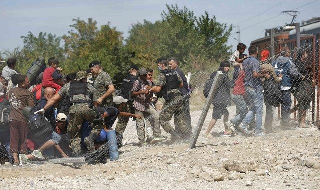 A fence breaks down as migrants push towards a train near Gevgelija, Macedonia, September 7, 2015. (Photo by Stoyan Nenov/Reuters)