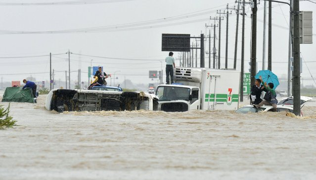 People wait for rescue on the roofs of cars as they are stranded on a road flooded by the Kinugawa river, caused by typhoon Etau in Joso, Ibaraki prefecture, Japan, in this photo taken by Kyodo September 10, 2015. (Photo by Reuters/Kyodo News)