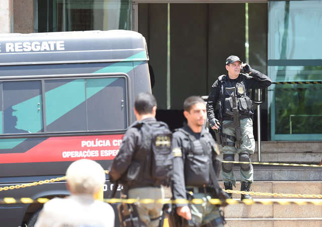 Police special forces are deployed at a hotel where an unidentified man keeps a hotel employee with an explosive-laden vest at a balcony of the hotel in Brasilia on September 29, 2014. (Photo by Evaristo Sa/AFP Photo)