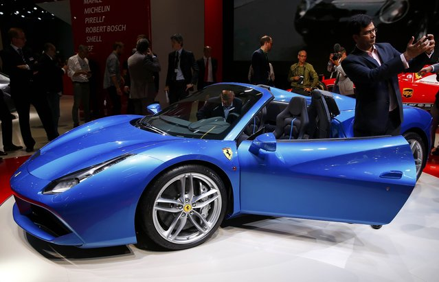 A visitor makes a selfie in front of a Ferrari car during the media day at the Frankfurt Motor Show (IAA) in Frankfurt, Germany, September 15, 2015. (Photo by Kai Pfaffenbach/Reuters)