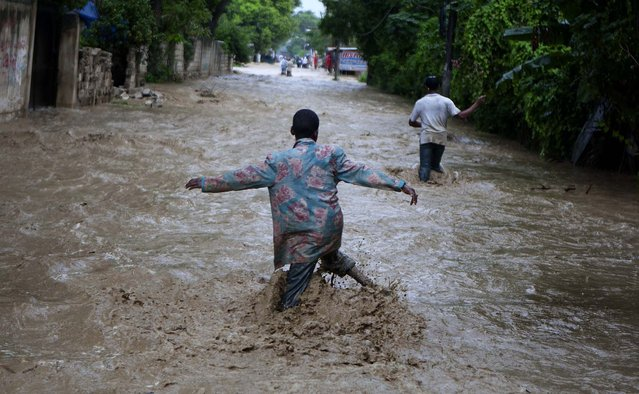 Residents wade through a street flooded by heavy rains from Hurricane Sandy in Port-au-Prince, Haiti. (Photo by Dieu Nalio Chery/Associated Press)