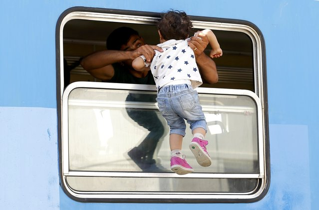 A migrant carries a child in a train at the station in Beli Manastir, Croatia September 18, 2015. (Photo by Laszlo Balogh/Reuters)