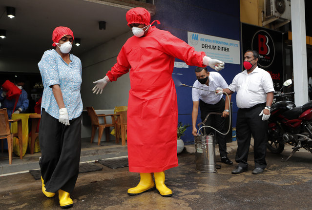 Sri Lankan Municipal health workers spray disinfectant to another colleague who conducted blood tests for COVID-19 antibody tests at a market place in Colombo, Sri Lanka, Friday, June 26, 2020. (Photo by Eranga Jayawardena/AP Photo)