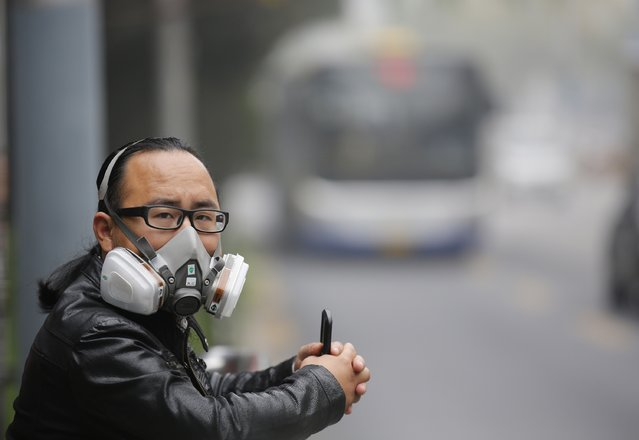 A man wearing a mask waits for a bus at a bus stand amid heavy haze and smog in Beijing, October 11, 2014. Widespread smog has affected a large part of north China including capital Beijing as the National Meteorological Center (NMC) extended a yellow alert on Thursday for air pollution, Xinhua News Agency reported. (Photo by Kim Kyung-Hoon/Reuters)