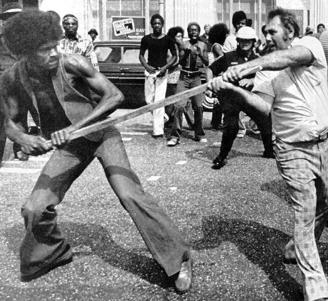 A member of the Ku Klux Klan and black man struggle over possession of a stick during an encounter in downtown Mobile, Alabama, Saturday, September 24, 1977. A large group of blacks disrupted the Klan's march, resulting in at least two encounters between the two groups. (Photo by AP Photo)