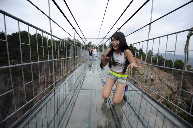 A woman plays around as she walks across a glass-bottomed suspension bridge in a scenic zone in Pingjiang county in southern China's Hunan province Thursday, September 24, 2015. The bridge, 300 meters (984 feet) long and 180 meters (590 feet), opened to visitors on Thursday for the first time since its conversion from a regular suspension bridge was completed. (Photo by Chinatopix Via AP Photo)