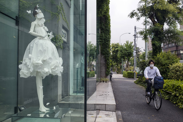A man wearing a protective mask to help curb the spread of the coronavirus passes by a window display of a dress on a mannequin with a similar mask, Friday, July 17, 2020, in Tokyo. The Japanese capital has confirmed Friday more than 290 new coronavirus cases. (Photo by Kiichiro Sato/AP Photo)