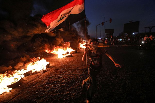 A protester runs holding an Iraqi flag as tires burn during a demonstration demanding better public services and jobs in Basra, southeast of Baghdad, Iraq, Monday, July 27, 2020. (Photo by Nabil al-Jurani/AP Photo)