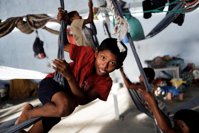 Indigenous Warao children from the Orinoco Delta in eastern Venezuela, play on hammocks at a shelter in Pacaraima, Roraima state, Brazil on November 23, 2017. (Photo by Nacho Doce/Reuters)