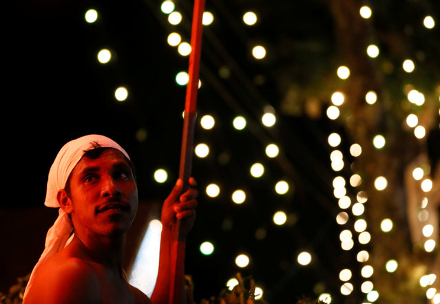 A torchbearer waits for the start of the annual Perahera (street pageant) at Rajamaha viharaya Buddhist temple in Colombo, Sri Lanka September 10, 2016. (Photo by Dinuka Liyanawatte/Reuters)