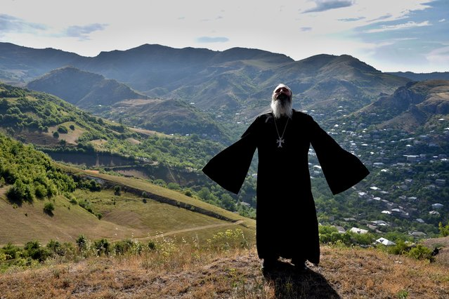 Priest Ter Abel prays for peace outside the village of Movses on the Armenian-Azerbaijani border on July 15, 2020. Defence officials in Armenia and Azerbaijan said fighting on their border subsided on July 15, 2020 after several days of deadly clashes raised fears of a major flare-up. At least 16 people on both sides were killed in three days of shelling that started Sunday between the ex-Soviet republics, which have been locked for decades in a conflict over Azerbaijan's separatist region of Nagorny Karabakh. (Photo by Karen Minasyan/AFP Photo)