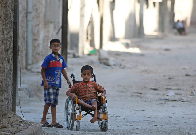 Boys, one of them in a wheelchair, go down a street in the rebel-held al-Sheikh Said neighbourhood of Aleppo, Syria September 1, 2016. (Photo by Abdalrhman Ismail/Reuters)