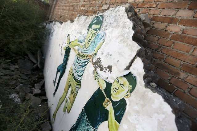 A work by Chinese artist ROBBBB is seen on a wall in the ruins of a building in Beijing September 27, 2015. (Photo by Jason Lee/Reuters)