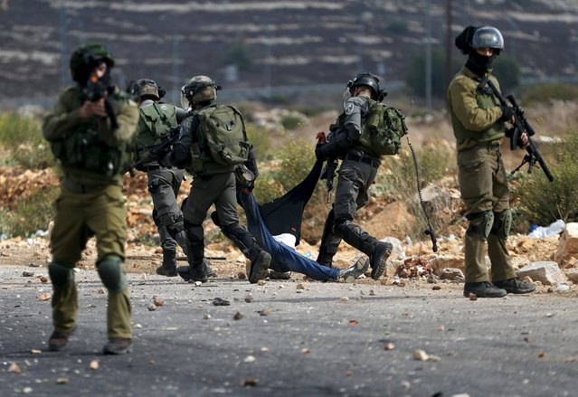 Israeli border police detain a wounded Palestinian protester during clashes near the Jewish settlement of Bet El, near the West Bank city of Ramallah, October 7, 2015. (Photo by Mohamad Torokman/Reuters)