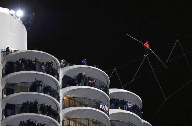 Daredevil Nik Wallenda performs his blindfolded walk along a tightrope between two skyscrapers suspended 500 feet  (152.4 meters) above the Chicago River in Chicago, Illinois, November 2, 2014. (Photo by Jim Young/Reuters)