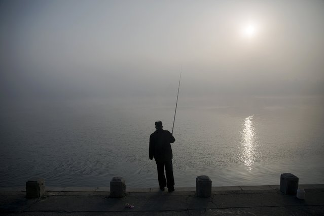 A man fishes amid morning fog over Taedong River in Pyongyang, North Korea October 8, 2015. (Photo by Damir Sagolj/Reuters)