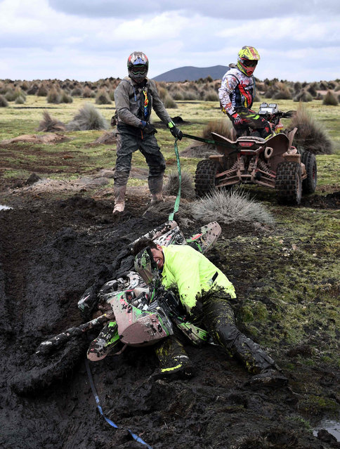 Chilean rider Patricio Cabrera is helped by other competitors during Stage 7 of the 2018 Dakar Rally between La Paz and Uyuni, Bolivia, on January 13, 2018. (Photo by Franck Fife/AFP Photo)
