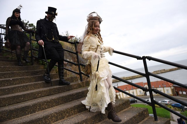 "People dressed in a gothic costumes attend the biannual ""Whitby Goth Weekend"" (WGW) festival in Whitby, Northern England, on November 2, 2014. The WGW festival brings thousands of goths and alternative lifestyle fans from the UK and around the world over a weekend of music, dancing and shopping. (Photo by Oli Scarff/AFP Photo)"