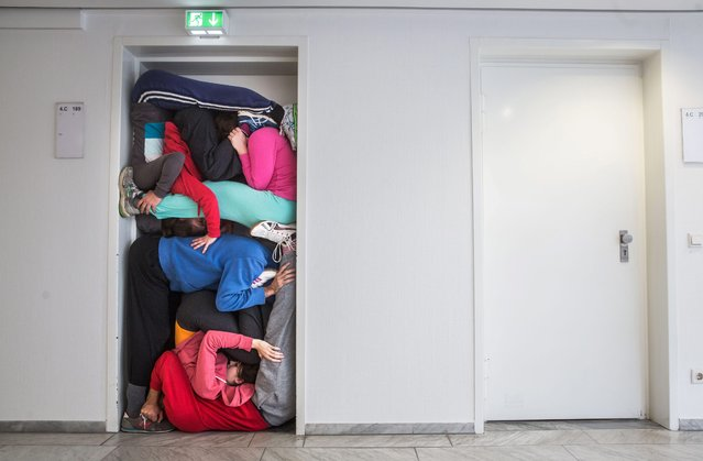 Members of a performance troupe led by Austrian choreographer Willi Dorner squeeze themselves into a doorway at the 2015 Frankfurt Book Fair, in Frankfurt am Main, Germany, 13 October 2015. The performance will be part of Austria's new cultural campaign on 14 October. Indonesia is the Guest of Honor country at the 2015 edition of the trade fair for books and media running from 14 to 18 October. (Photo by Frank Rumpenhorst/EPA)