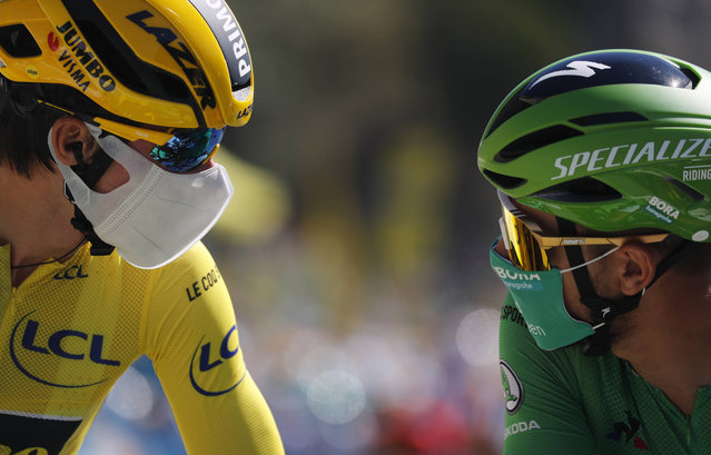 Slovenia's Primoz Roglic, wearing the overall leader's yellow jersey speaks with Slovakia's Peter Sagan, wearing the best sprinter's green jersey at the start of the tenth stage of the Tour de France cycling race over 168.5 kilometers (104.7 miles) from Ile d'Oleron to Ile de Re, France, Tuesday, September 8, 2020. (Photo by Thibault Camus/AP Photo)