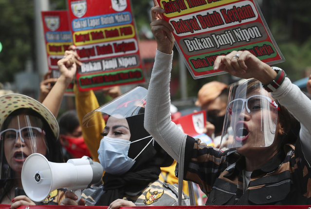 Entertainment workers wearing face shields as the precaution against coronavirus outbreak, take part in a protest against the large-scale restrictions imposed by the city government that requires the temporary closure of entertainment places,  outside the city hall in Jakarta, Indonesia, Monday, October 5, 2020. (Photo by Achmad Ibrahim/AP Photo)