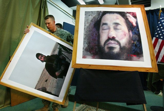 A U.S. soldier at a press conference in Baghdad, Iraq, takes down an older image, to display the latest image purporting to show the body of Abu Musab al-Zarqawi, the al-Qaida-linked militant who led a bloody campaign of suicide bombings, kidnappings and hostage beheadings in Iraq. Zarqawi was killed in a U.S. airstrike, Iraq's Prime Minister Nouri al-Maliki announced on June 8, 2006. (Photo by Khalid Mohammed/AP Photo/The Atlantic)
