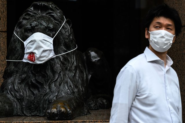 A man wearing a face mask walks past a faced mask-clad lion statue of a department store in Ginza district of Tokyo on September 29, 2020. (Photo by Philip Fong/AFP Photo)