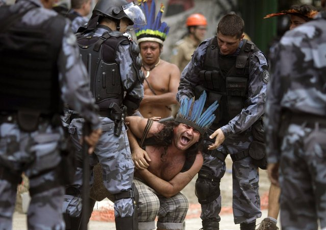A native Indian reacts as military police officers evict a native Indian community living at the Brazilian Indian Museum in Rio de Janeiro March 22, 2013. Brazilian military police took position early morning outside the abandoned museum, where the community of around 30 native Indians have been living in since 2006. The community was ordered to leave the museum in 72 hours by court officials since last week, local media reported. Most of the Indians later left the museum after making a deal with the authorities. (Photo by Ricardo Moraes/Reuters)