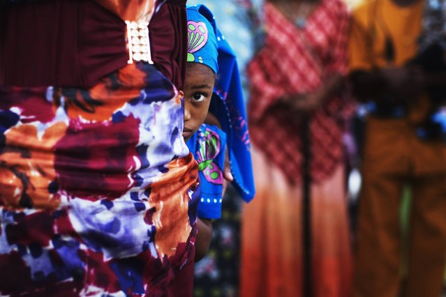 """A girl from the African Hebrew Israelite community, popularly known as """"the Black Hebrews"""", hides behind an adult during a celebration for the holiday of Shavuot in the southern town of Dimona, in this June 15, 2014 file photo. (Photo by Finbarr O'Reilly/Reuters)"""