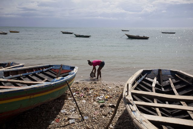 A woman takes water from the sea before the arrival of Hurricane Matthew in Arcahaie, Haiti. Sunday October 2, 2016. A powerful Hurricane Matthew moved slowly Sunday across the Caribbean Sea on a track that authorities warned could trigger devastation in parts of Haiti. (Photo by Dieu Nalio Chery/AP Photo)