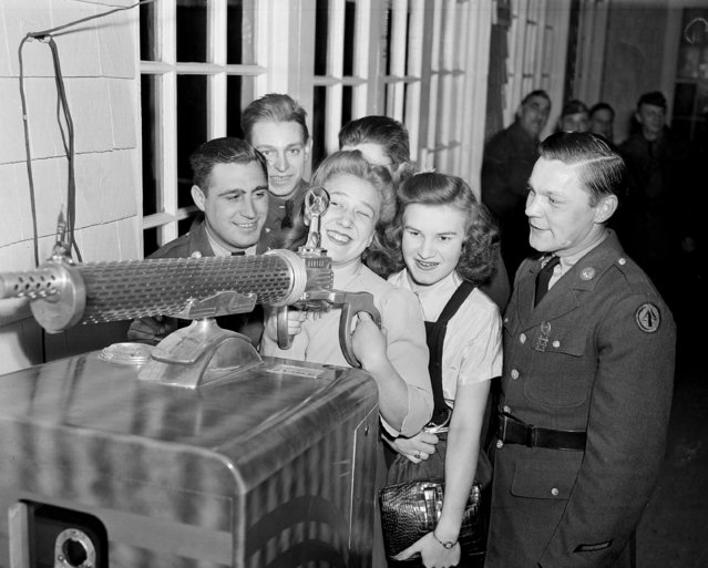 Soldier boys at Fort Dix, N.J., learn something about guns during their working hours, as they show their girlfriends at a camp dance, December 13, 1940. In front row, playing with the coin amusement gun, from left: Pvt. Tom D'Amato of West Orange; Rose Sinkewicz, behind gun site, of Trenton; Julia Ivans of Trenton, and Pvt. Vernon Landers of Kearney. Back row: Pvts. William Sargent and William Corlies of Philadelphia. (Photo by AP Photo)