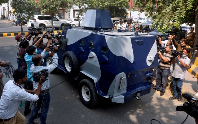Video journalists film an armored vehicle carrying Abid Malhi, a key assailant suspected in the gang rape of a woman on a desolate highway, following his court appearance in Lahore, Pakistan, Tuesday, October 13, 2020. Police arrested a key suspect in a brutal rape of a woman whose car broke down on a deserted highway major highway near the eastern city of Lahore last month. (Photo by K.M. Chaudary/AP Photo)