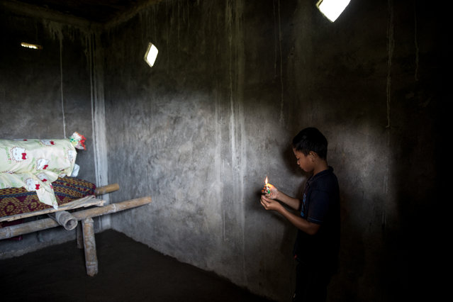 A boy lights incense in front of Lucas Payung's body before the Ma'Nene ritual in Barrupu Village, Toraja, South Sulawesi on August 16, 2016. (Photo by Agung Parameswara/The Washington Post)