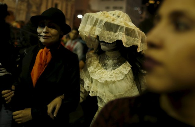 "A couple dressed up as ""Catrinas"", a Mexican character also known as ""The Elegant Death"", take part in a Catrinas parade in Mexico City October 31, 2015. (Photo by Carlos Jasso/Reuters)"