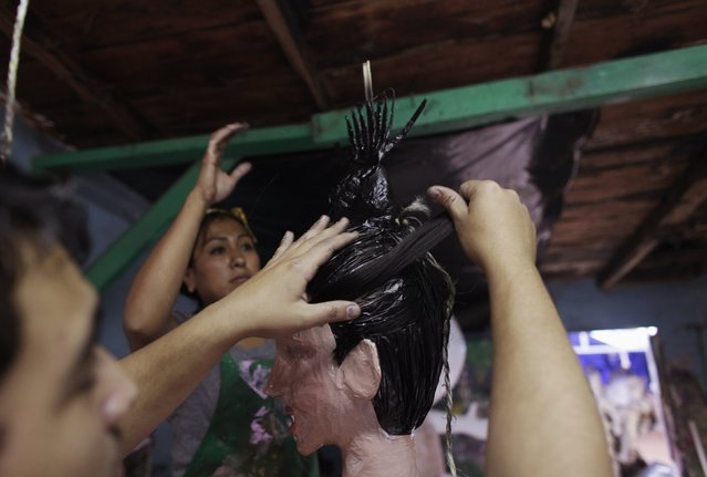 Mexican artisan Dalton Ramirez (L) attaches artificial hair to the head of a pinata depicting TV celebrity Kim Kardashian at his workshop in Reynosa December 6, 2014. (Photo by Daniel Becerril/Reuters)