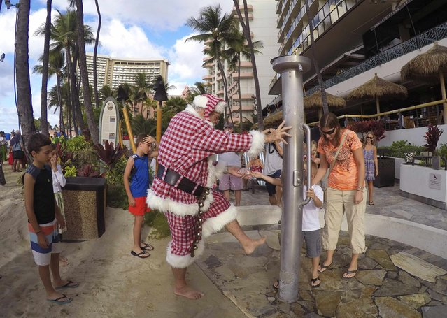 Donald Boyce, dressed up like Santa Claus, washes the sand off his feet after going outrigger canoe surfing off Waikiki beach in Honolulu, Hawaii December 13, 2014. (Photo by Hugh Gentry/Reuters)