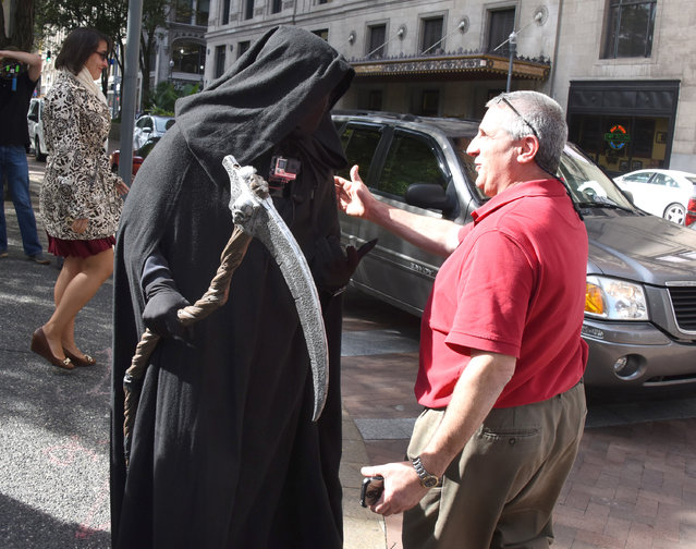 """In an October 10, 2016 photo, the """"Grim Reaper"""" meets Mark Caparelli , of Whithall, Pa., during his lunch break along Grant Street in Pittsburgh. Mark was not using his cell phone. (Photo by Darrell Sapp/Pittsburgh Post-Gazette via AP Photo)"""