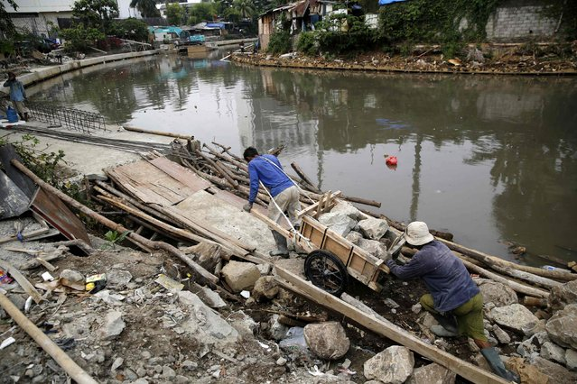 Labourers move stones to reinforce one of the city's many canals to help prevent flooding in Central Jakarta October 28, 2014. (Photo by Darren Whiteside/Reuters)