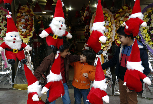 Palestinian children play next to a stand selling toys of Father Christmas in Gaza City on December 24, 2014, as Christians around the world prepare to celebrate Christmas. For many faithful across the region, the festivities will be tinged with sadness following a year of bloodshed marked by a surge in the persecution of Christians that has drawn international condemnation. (Photo by Mohammed Abed/AFP Photo)