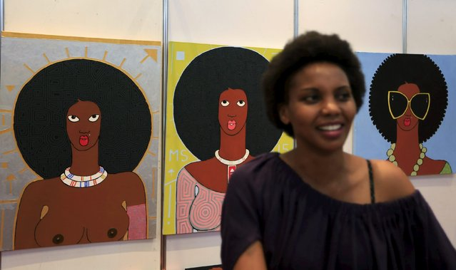 Curator Jackie Muti stands next to paintings by Kenyan artist Michael Soi at the Kenya Art Fair 2015 exhibition at the Sarit Centre in Kenya's capital Nairobi November 14, 2015. With growing interest from international auction houses and a flourishing gallery scene at home, East African art is catching on with global collectors and a new generation of local buyers. (Photo by Noor Khamis/Reuters)
