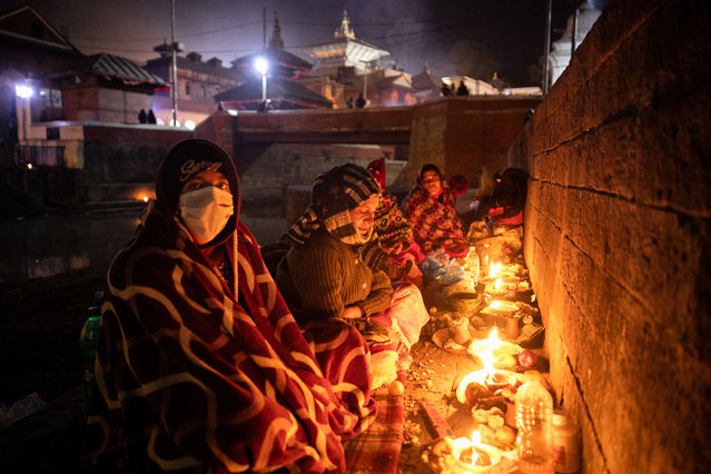 """Hindu devotees sit next to oil lamps as they perform rituals in memory of their deceased family members during the """"Bala Chaturdashi"""" festival at the Pashupatinath Templein Kathmandu, Nepal on December 13, 2020. Nepalese Hindu Devotees celebrate the festival by lighting oil lamps and scattering seven types of grains known as """"sat biu"""" along a route at the temple to honors the departed. (Photo by Prabin Ranabhat/SOPA Images/Rex Features/Shutterstock)"""