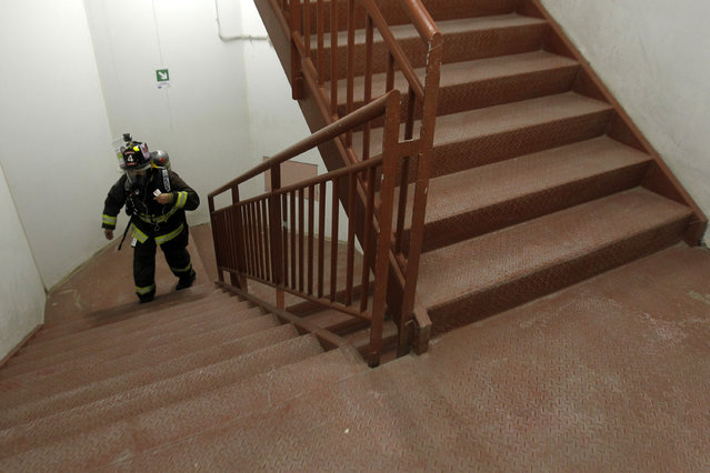 """A firefighter climbs through the stairs of the Costanera Centre Tower in Santiago as part of the """"Race for Life"""" aimed at encouraging organ donation in Chile, on October 16, 2016. (Photo by Claudio Reyes/AFP Photo)"""