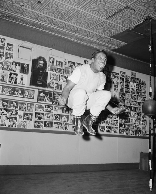 "Middleweight Champion Sugar Ray Robinson breaks into a laugh as he skips rope while training for his title bout with Gene Fullmer at a gymnasium in New York on December 28, 1956 . Robinson was reported in ""excellent condition"" for the big fight. (Photo by AP Photo)"