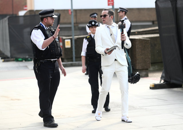 Police officers speak with a man who was preaching outside St Thomas' hospital as the spread of the coronavirus disease (COVID-19) continues, London, Britain, April 8, 2020. (Photo by Simon Dawson/Reuters)
