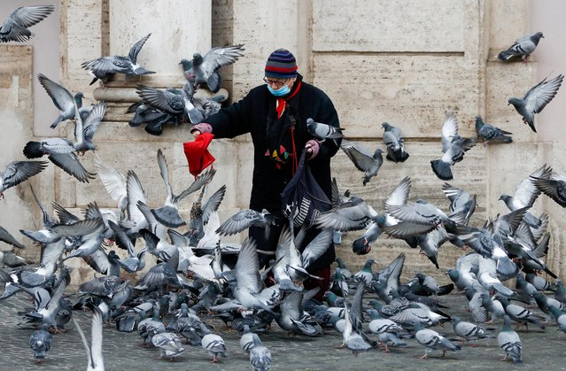A person feeds pigeons at Piazza Navona, as the region enters the 'yellow zone' after the government relaxed some of the coronavirus disease (COVID-19) curbs on weekdays following a strict lockdown over the holidays, in Rome, Italy on January 7, 2021. (Photo by Yara Nardi/Reuters)