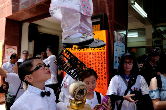 A child looks up to his partner as she stands above the crowd with the support of an elaborate rig of hidden metal rods, during the Bun Festival parade at Cheung Chau island in Hong Kong on May 22, 2018. (Photo by Bobby Yip/Reuters)